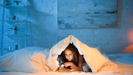 Photo for Child under blanker reading book and holding flashlight - Royalty Free Image