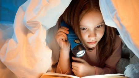 Photo for Kid holding flashlight and reading book under blanket in bedroom - Royalty Free Image