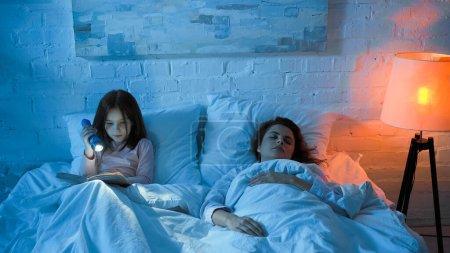Photo pour Femme dormant près d'un enfant lisant un livre sur son lit la nuit - image libre de droit