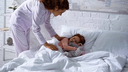 Woman in pajama standing near child sleeping on bed