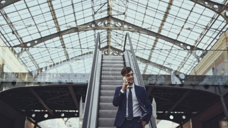 happy businessman in glasses talking on smartphone and standing with hand in pocket on escalator