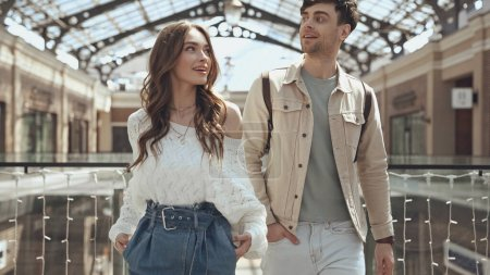 Photo pour Happy woman and man posing with hands in pockets in shopping mall - image libre de droit