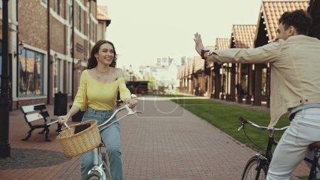 happy man waving hand near woman riding bicycle on street