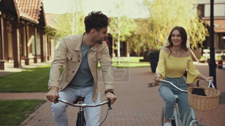 smiling man and woman riding bicycles on street
