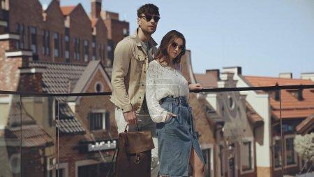 stylish couple in sunglasses posing outside