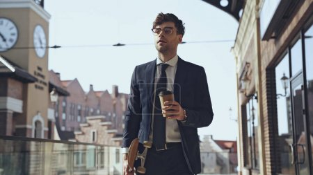 Photo for Businessman in suit holding coffee to go and walking with penny board in shopping mall - Royalty Free Image