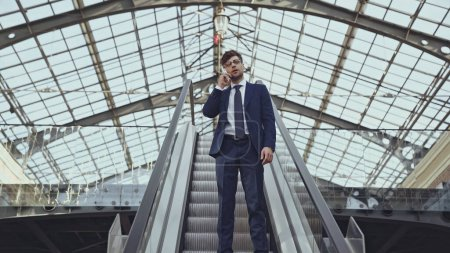 low angle view of businessman in glasses using smartphone on escalator