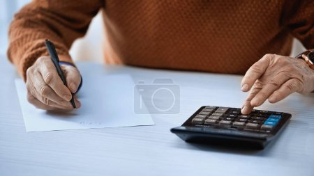 Ausgeschnittene Ansicht eines älteren Mannes mit Taschenrechner und Schreiben mit Stift auf grauem Hintergrund