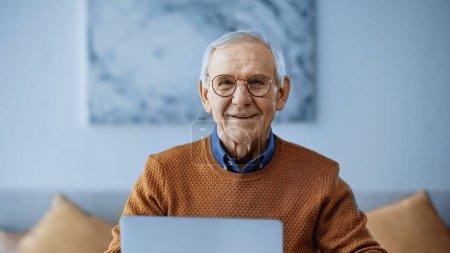 Photo pour Homme âgé souriant assis avec ordinateur portable à la maison - image libre de droit