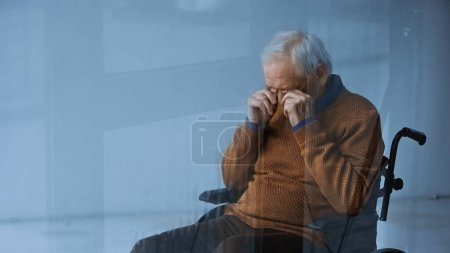 senior man in wheelchair covering eyes with hands on grey background behind rainy glass