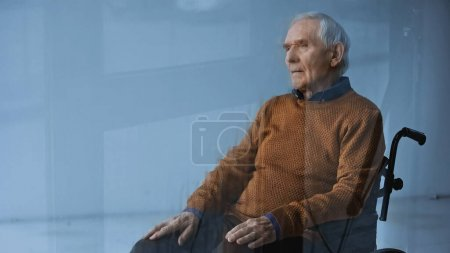 thoughtful senior man in wheelchair looking away on grey background