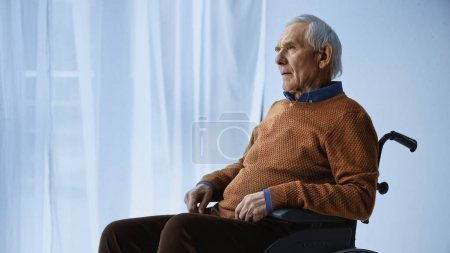 dreamy senior man in wheelchair sitting at retirement home