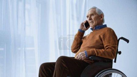 elderly man in wheelchair speaking on cellphone at retirement home