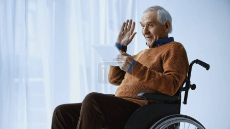 cheerful pensioner in wheelchair waving hand and having video call on tablet at retirement home