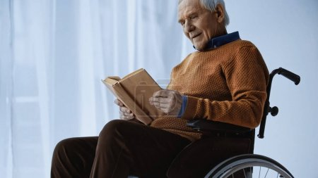 senior man sitting in wheelchair and reading book at retirement home