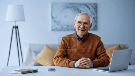 Photo for Happy elderly man sitting with clenched hands at table with laptop and cellphone in living room - Royalty Free Image