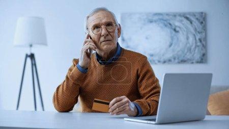 Photo pour Homme âgé sérieux assis avec carte de crédit près d'un ordinateur portable et parler sur un téléphone portable à la maison - image libre de droit