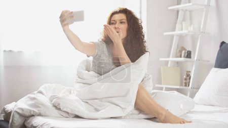 Photo for Positive young woman sending air kiss while taking selfie on smartphone in bedroom - Royalty Free Image