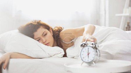 éveillé jeune femme éteindre rétro réveil