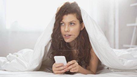 Photo pour Chère jeune femme en utilisant smartphone tout couché sous la couverture - image libre de droit