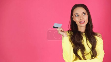 Photo pour Thoughtful young adult woman holding credit card isolated on pink - image libre de droit
