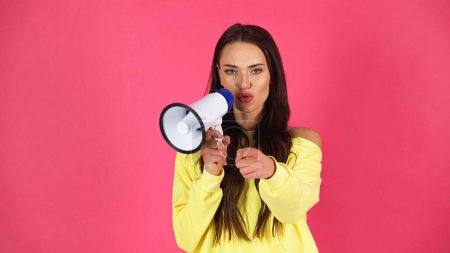 young adult woman making promotion with loudspeaker and pointing with finger at camera isolated on pink