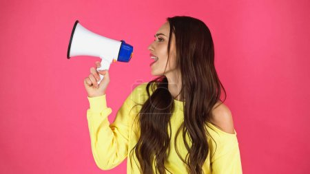 young adult woman making promotion with loudspeaker isolated on pink