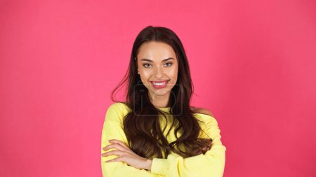 smiling young adult woman in yellow sweatshirt standing with crossed arms isolated on pink