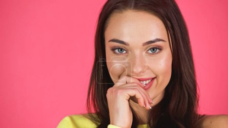 Photo pour Portrait of shy smiling young adult woman isolated on pink - image libre de droit