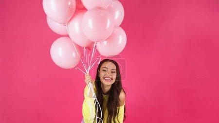 Photo for Joyful young adult woman in yellow sweatshirt holding balloons isolated on pink - Royalty Free Image