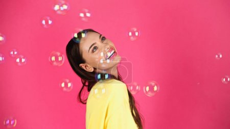 happy young adult woman in yellow blouse with soap bubbles on pink background