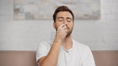allergic man with closed eyes using nasal spray at home
