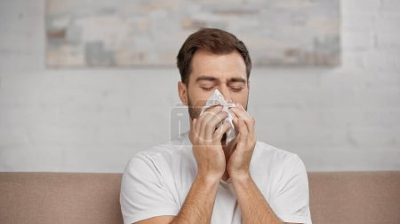 Photo for Man with pollen allergy sneezing in napkin at home - Royalty Free Image