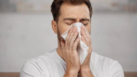man with allergy sneezing in napkin at home