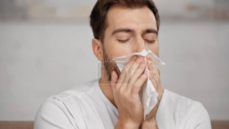 man with allergy sneezing in tissue at home