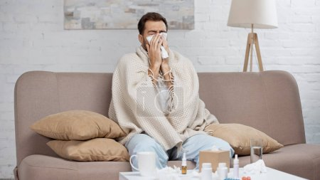 Photo for Sick man sitting on sofa and sneezing in tissue near coffee table with drinks and bottles - Royalty Free Image