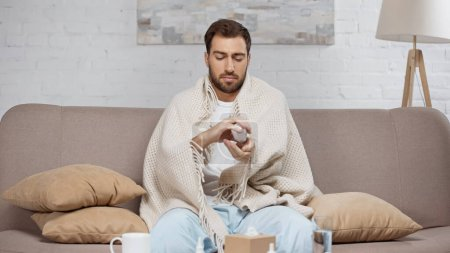 Photo for Sick man sitting on sofa and holding bottle with pills near coffee table with drinks - Royalty Free Image