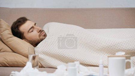 Photo pour Sick man lying under blanket near medication and crumpled tissues - image libre de droit