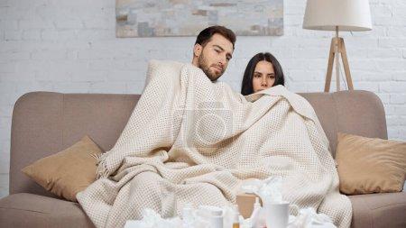 Photo pour Sick couple under blanket in living room - image libre de droit