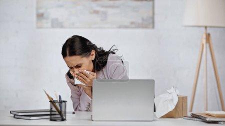 Photo pour Allergic businesswoman sneezing in napkin near laptop on desk - image libre de droit