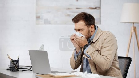 Photo pour Allergic businessman sneezing in napkin near laptop on desk - image libre de droit