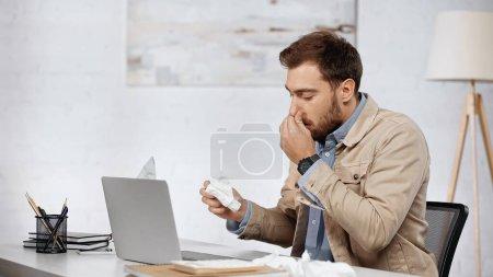 Photo pour Allergic businessman with running nose sneezing near laptop on desk - image libre de droit