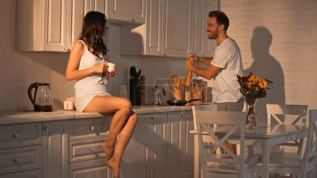 Photo pour Joyful woman sitting on kitchen cabinet with cup near boyfriend with paper shaker - image libre de droit
