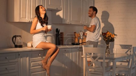 Photo pour Cheerful woman sitting on kitchen cabinet with cup near boyfriend with coffee pot - image libre de droit