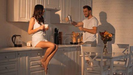 Photo pour Brunette woman sitting on kitchen cabinet with cup near boyfriend with coffee pot - image libre de droit