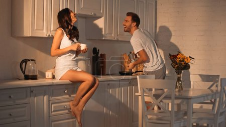 Photo pour Happy woman sitting on kitchen cabinet with cup and laughing with boyfriend - image libre de droit