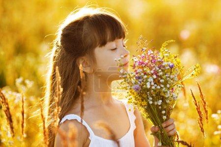 Photo pour Happy little girl with a bouquet of wild flowers - image libre de droit