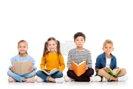 Photo pour Enfants positifs multiethniques tenant des livres tout en étant assis sur fond blanc - image libre de droit