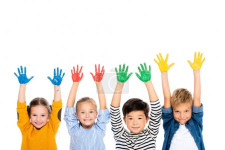 Cheerful multiethnic kids with hands in colorful paint looking at camera isolated on white