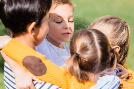 Photo for Boy hugging multiethnic friends on blurred foreground outdoors - Royalty Free Image